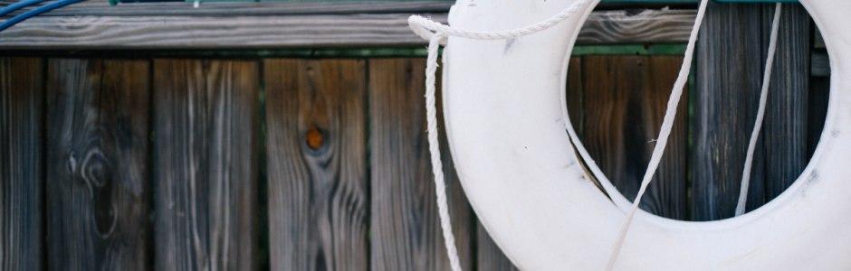 weisser rettungsring auf holzschiff